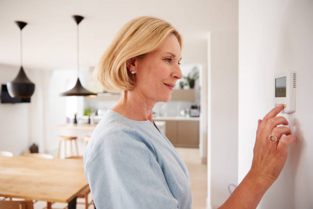 Close Up Of Mature Woman Adjusting Central Heating Temperature At Home On Thermostat stock photo
