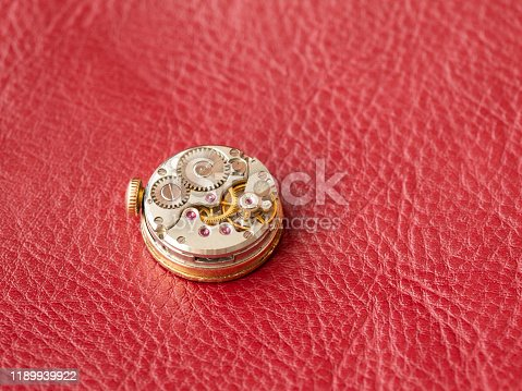 Clock mechanism with gears on red leather background
