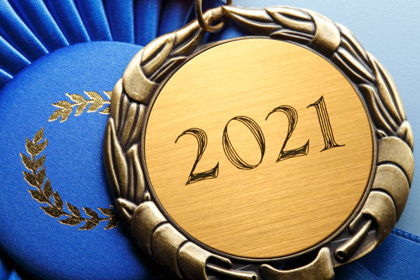 """Close Up Of Medal Engraved With """"2021"""" Resting On A Blue Ribbon stock photo"""