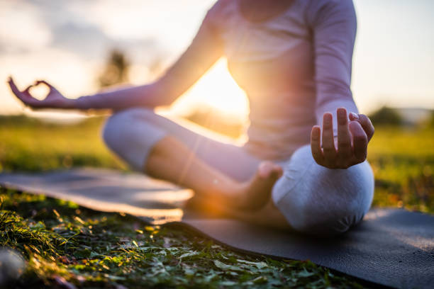 Close up of meditation in park at sunrise. Close up of yoga outdoor at sunset. wellbeing stock pictures, royalty-free photos & images