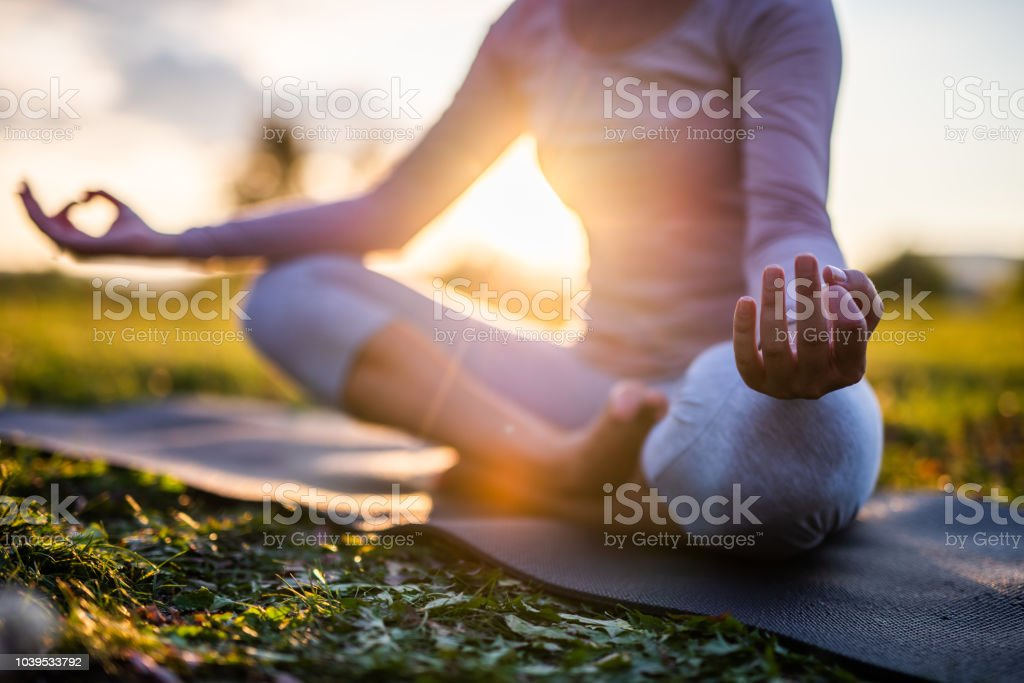 Close up of meditation in park at sunrise. stock photo