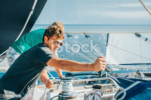 istock Close up of men at rudder on sailing boat, Croatia 1094597488