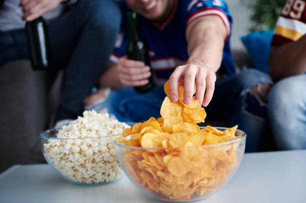 Close up of mens hand grabbing chips stock photo