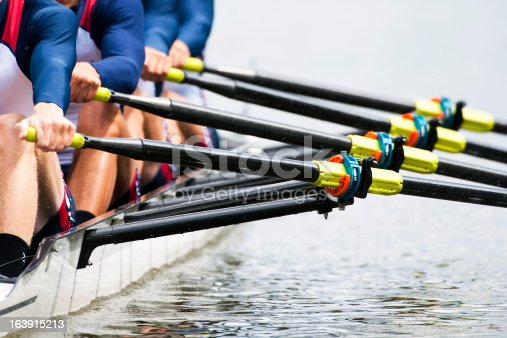 Close up of a men's quadruple skulls rowing team, seconds after the start of their race