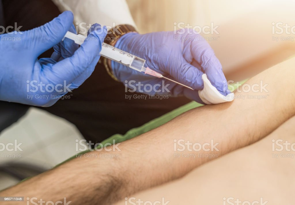 Close up of mid adult man taking a vaccine. stock photo