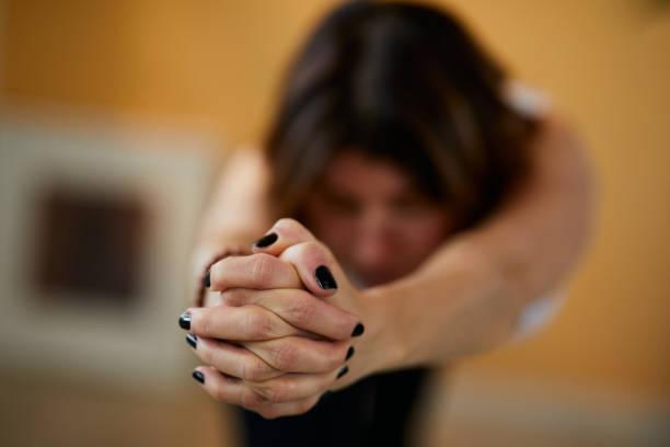 close up of middle aged brunette doing yoga at home. selective focus on hands. - mão no chakras velas imagens e fotografias de stock