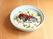 istock Close up of milky fish head soup in bowl on table, traditional Chinese delicious food. 1202886651
