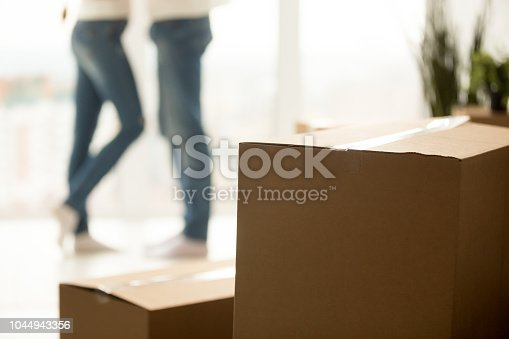 938682826istockphoto Close up of millennial couple moving to new home with boxes 1044943356