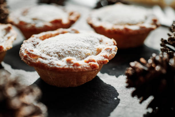 Close up of Mince Pies with festive Pine Cones in strong natural light against a slate background. stock photo