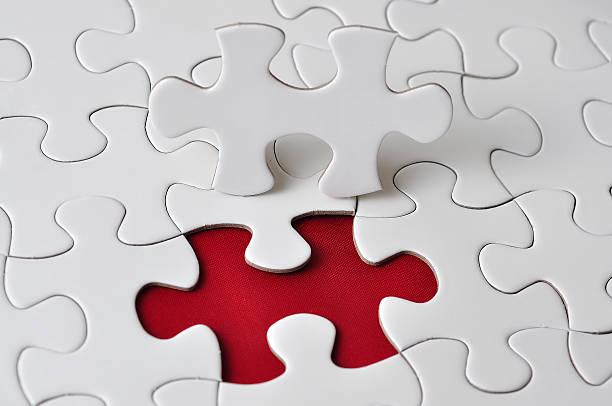 Nahaufnahme des fehlenden Puzzle auf rotem Hintergrund, Geringe Tiefenschärfe – Foto