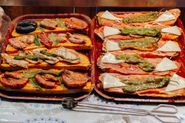 close up of mixed platter with toasts: meat ,peppers cheese, sausages, spicy sausage, black pudding and tomato spread on bread - confiture tomatoes imagens e fotografias de stock