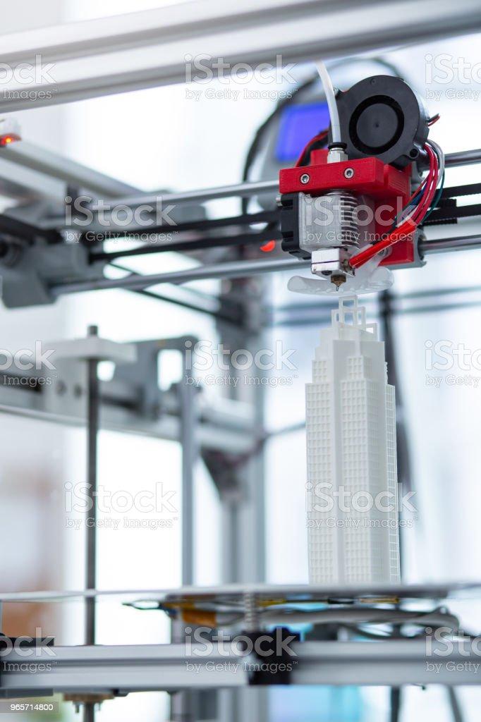 Close up of modern 3D printer creating skyscraper model - Royalty-free 3D Printing Stock Photo