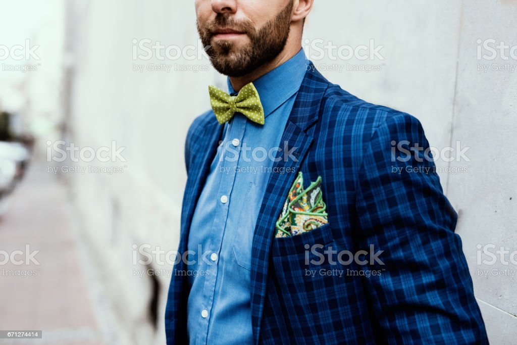 Close up of modern hipster's upper body wearing navy blue checkered jacket, blue shirt, green bow tie and in his pocket a colorful handkerchief stock photo