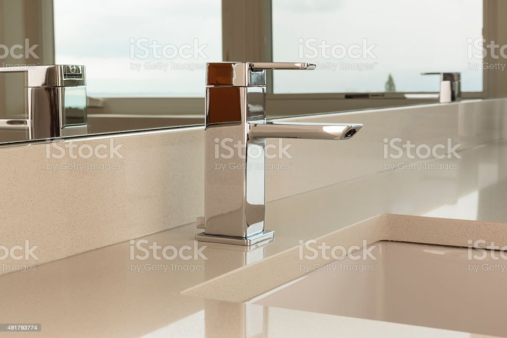 A modern, sleek, chrome faucet, close up in an empty bathroom
