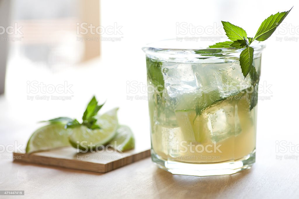 Close up of mojito glass with lemon slices blurred in back stock photo