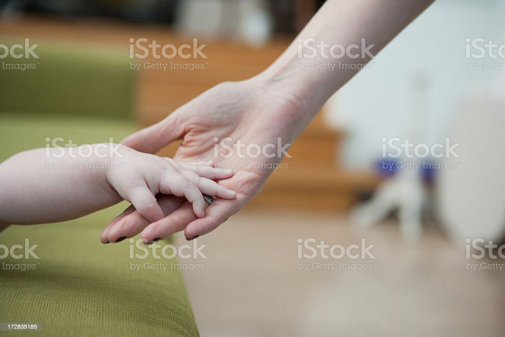 Close up of mother and baby son holding hands royalty-free stock photo