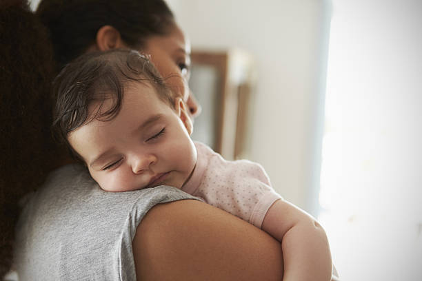 Close Up Of Mother Cuddling Sleeping Baby Daughter At Home - foto stock