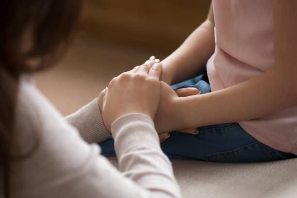 il primo tempo delle mani della madre copre le mani della figlia piccola - protezione foto e immagini stock