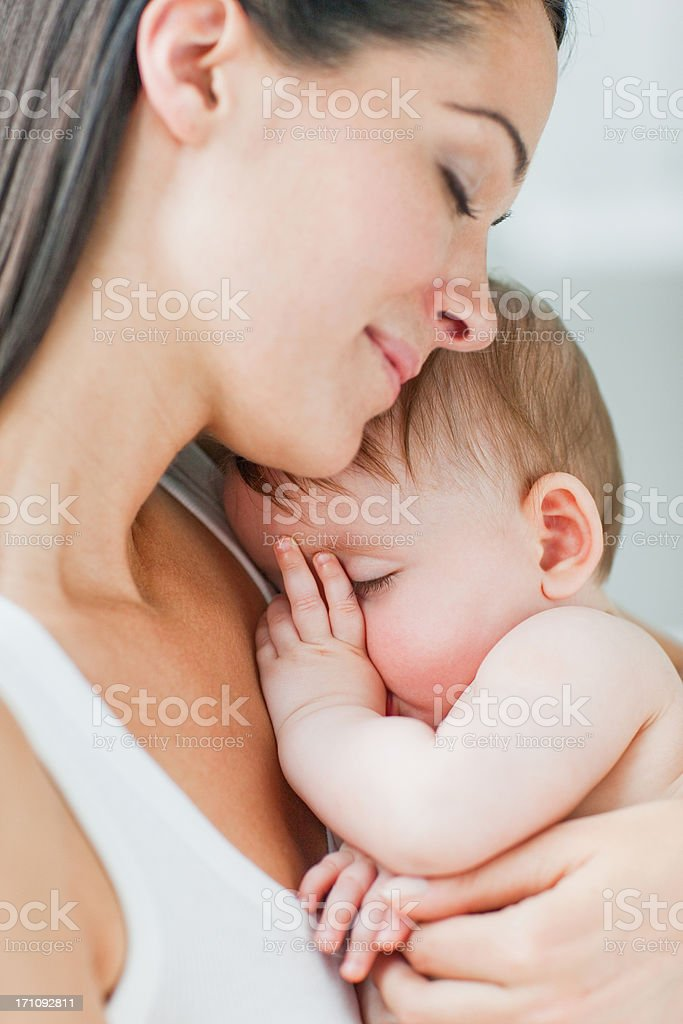Close up of mother holding sleeping baby sucking thumb stock photo