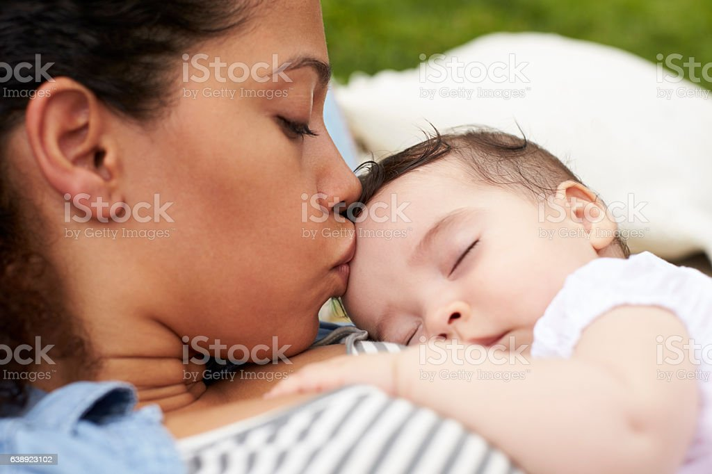 Close Up Of Mother With Baby Relaxing On Rug In Garden stock photo