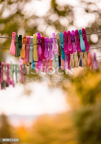Close up image depicting multi colored plastic clothing pegs hanging on a clothes line outdoors. In the background green foliage is blurred out of focus. Vertical color image with copy space.