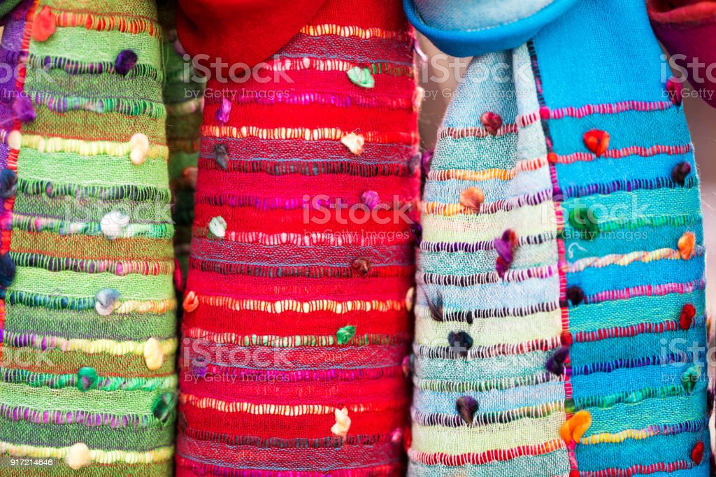 Close up of multi colored womens scarves and pashmina shawls patterned fabrics for sale at market stock photo