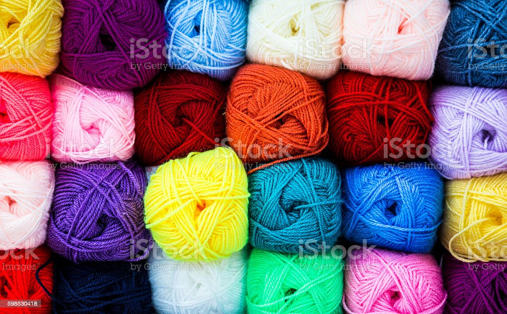 Close up of multi coloured balls of wool in a row stock photo