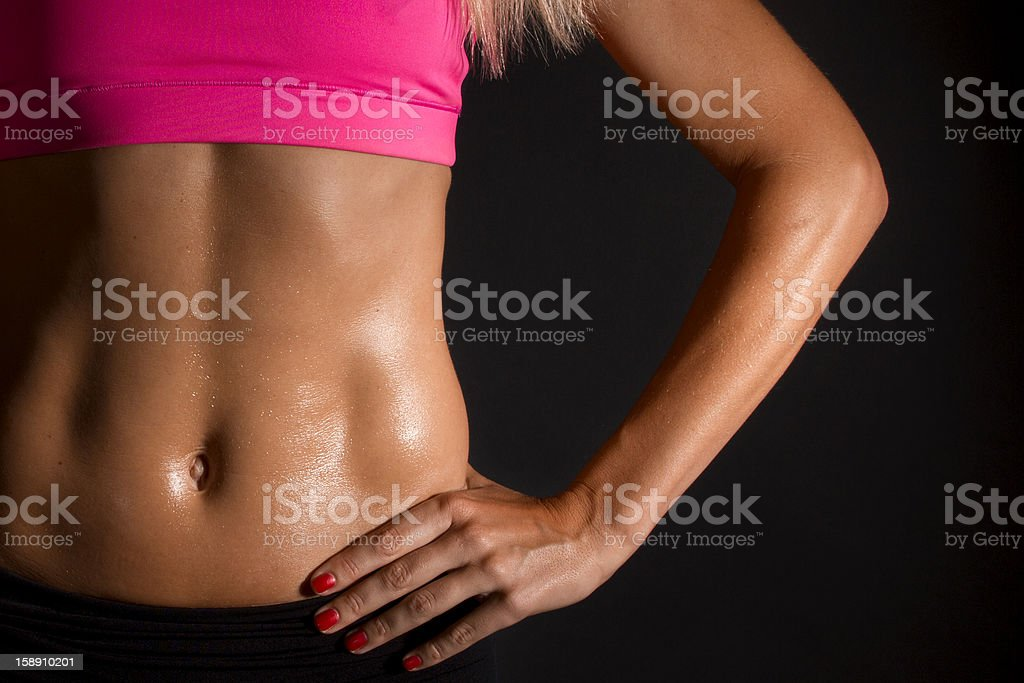 Close Up of Muscular Female Abs on Black Background stock photo