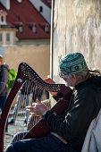 Close up of musician playing a harp at Prague Castle.