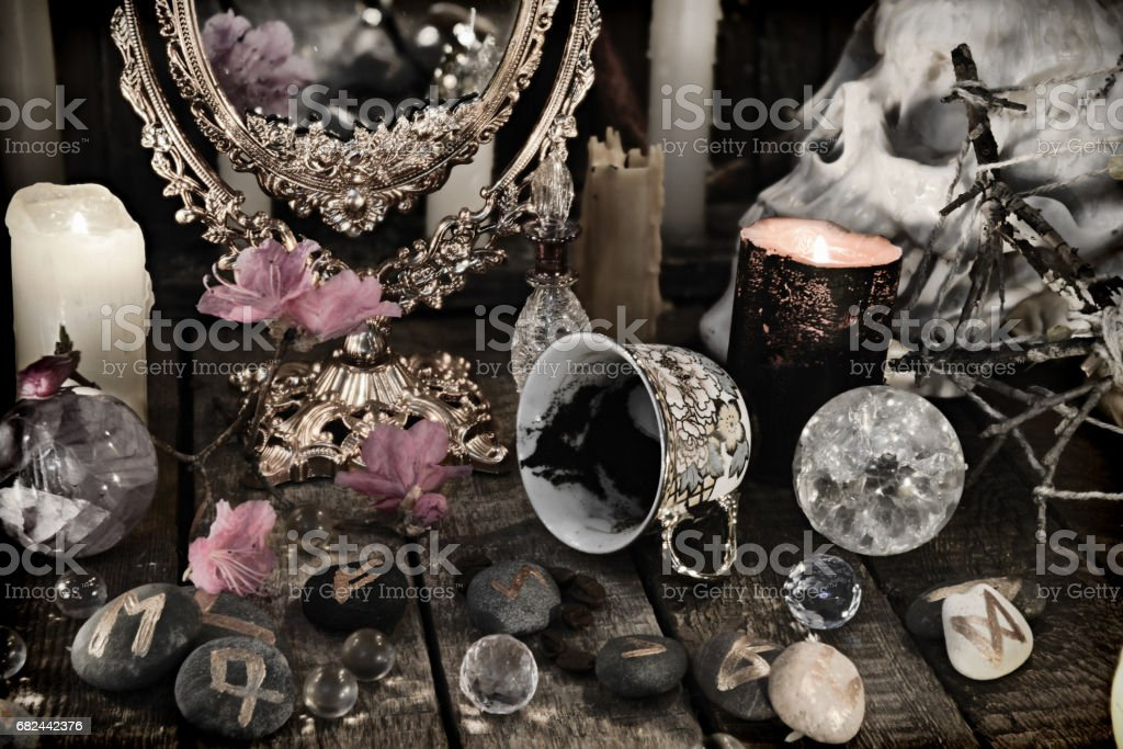 Close up of mystic objects, skull and pink flowers royalty-free stock photo