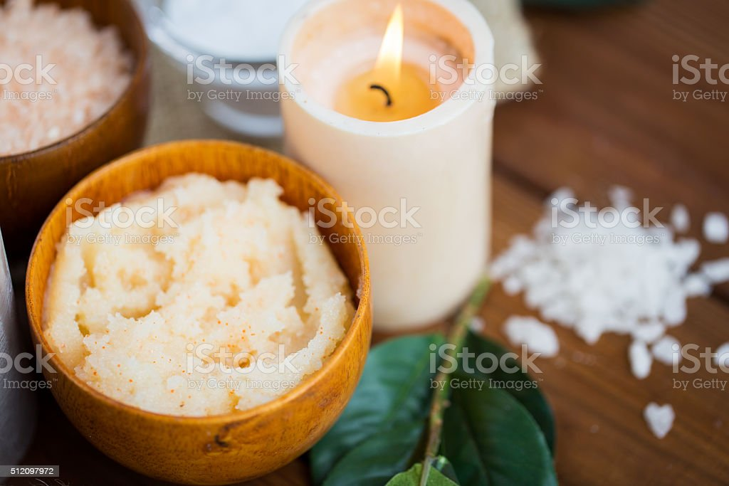 close up of natural body scrub and candle on wood stock photo