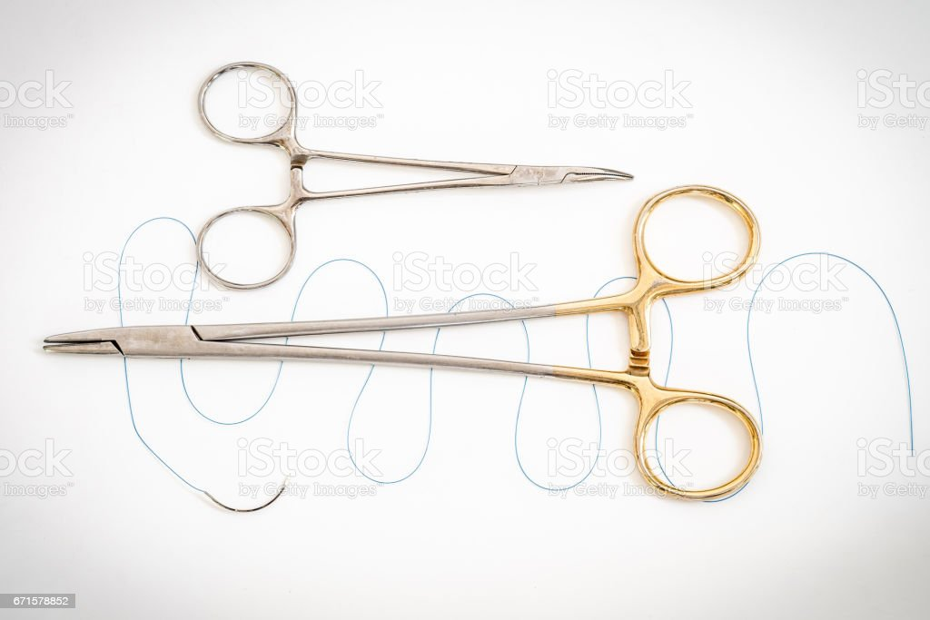 Close up of needle holder with suture and needle stock photo