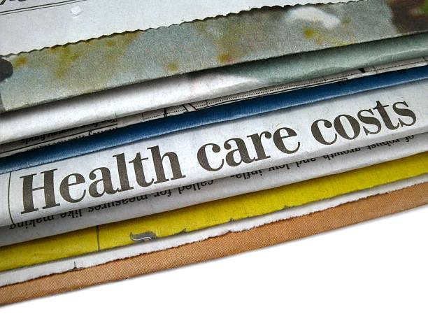 Close up of newspaper headline reading health care costs  stock photo
