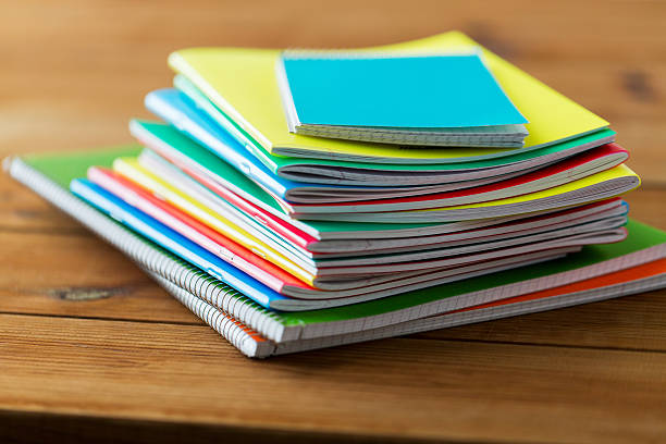 close up of notebooks on wooden table education, school supplies and object concept - close up of notebooks on wooden table workbook stock pictures, royalty-free photos & images