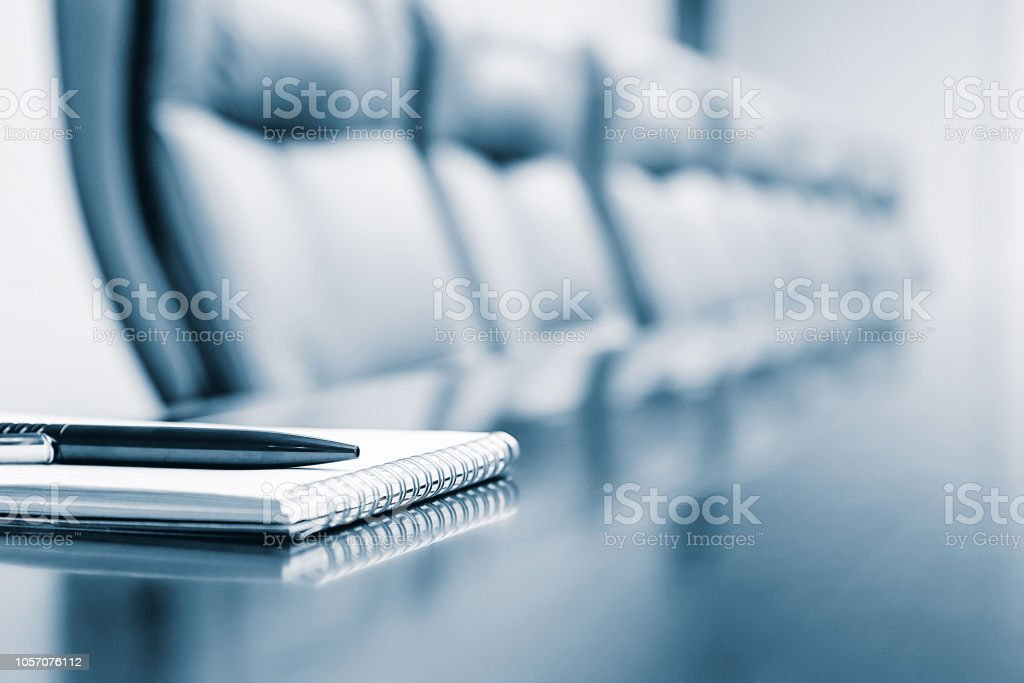 Close up of notepad kept on table in empty room stock photo