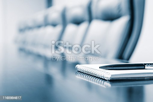 Notepad kept on table in empty conference room