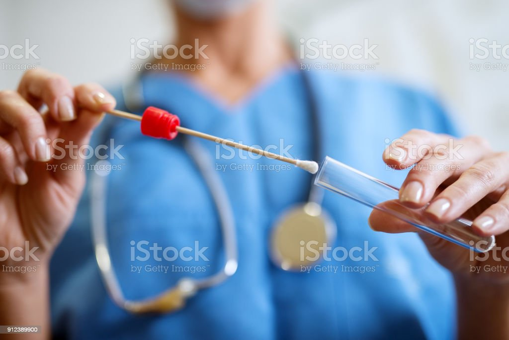 Close up of nurses hands holding buccal cotton swab and test tube ready to collect DNA from the cells. stock photo