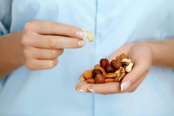 close up of nuts in woman hands. - frutos secos imagens e fotografias de stock