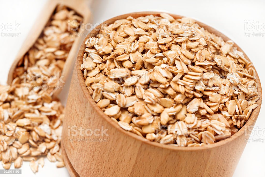 Close up of oatmeal in bowl and scoop stock photo