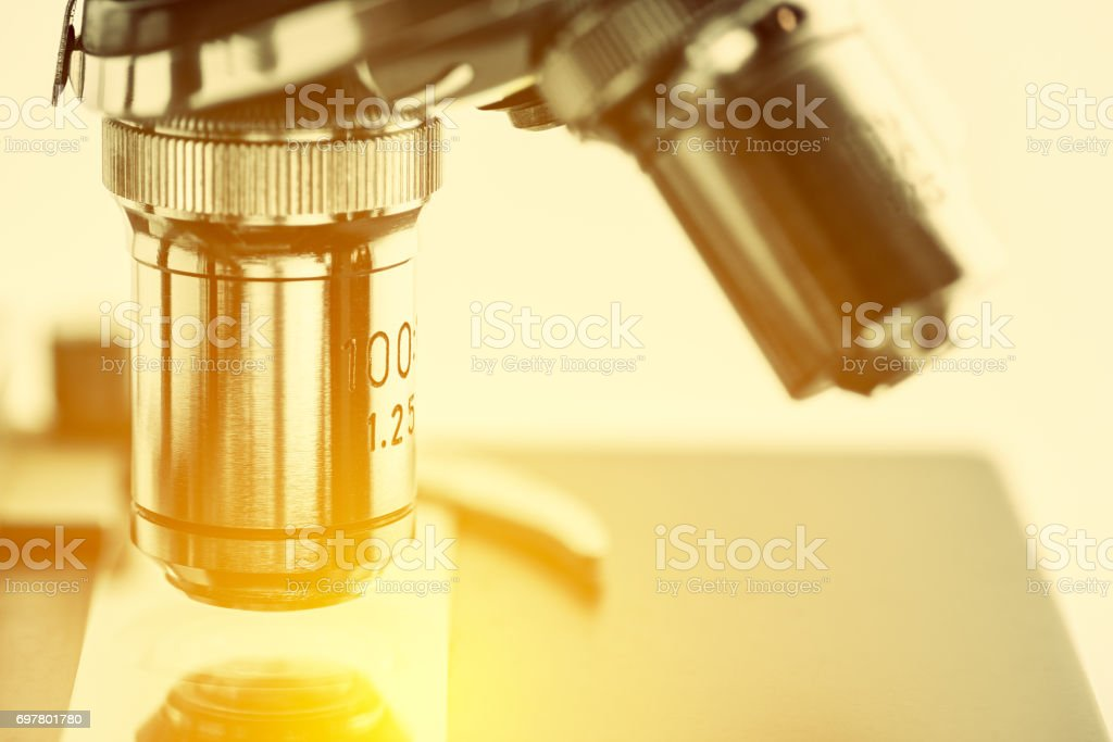 Close up of objective lenses with a microscope slide. stock photo