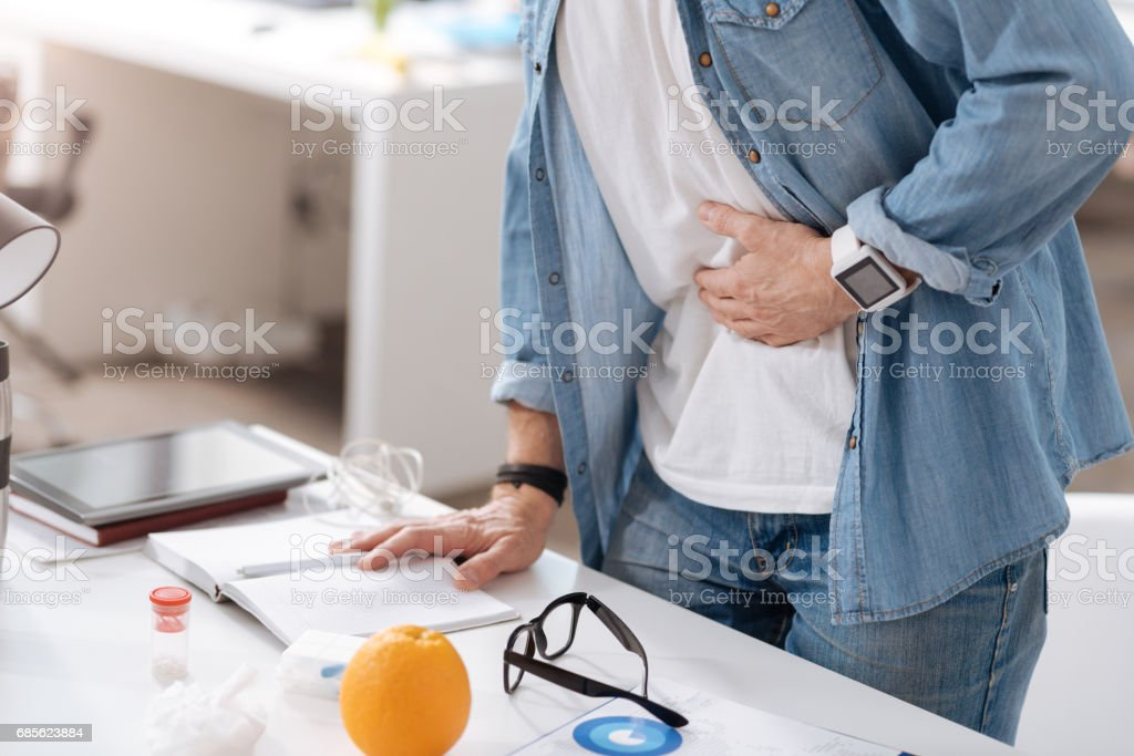Close up of office worker putting left hand on belly stock photo