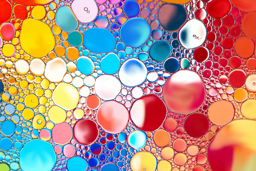 Close up of oil drop on water surface. Abstract background.