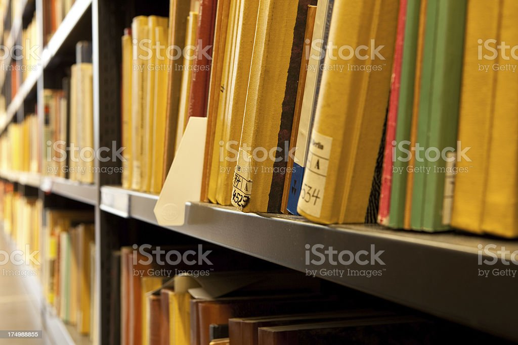 Close up of old books spines in a library shelf stock photo
