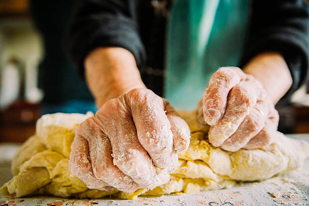 close up of old  italian lady's hands making italian pasta stock photo
