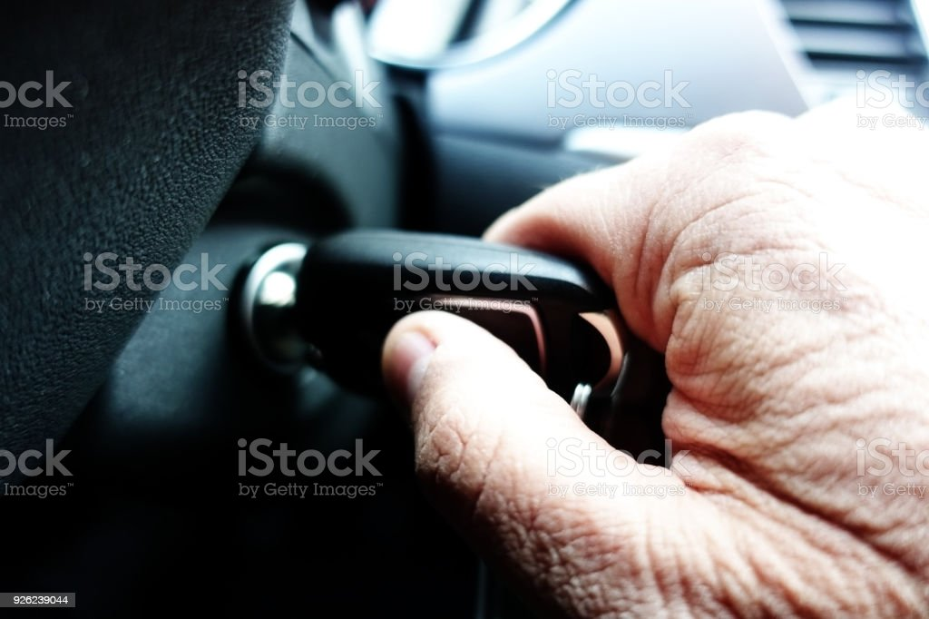 Close up of old man hand turning on the car engine stock photo