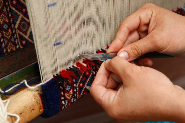 Close up of old woman weaving colorful pattern on loom stock photo
