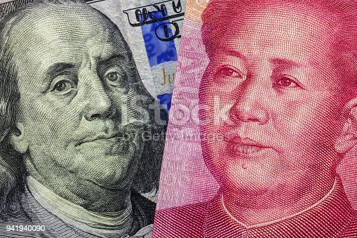 istock Close up of one hundred Dollar and 100 Yaun banknotes with focus on portraits of Benjamin Franklin and Mao Tse-tung/USA vs China trade war concept 941940090