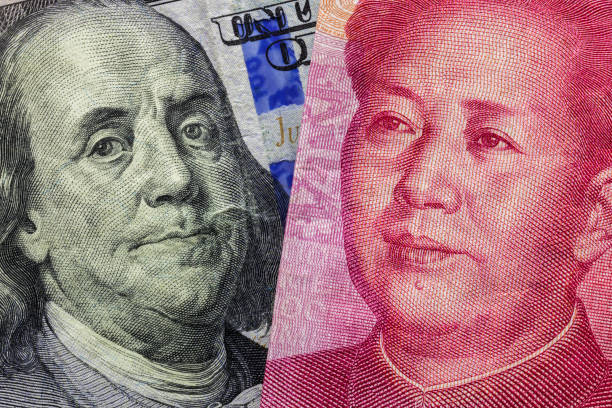 Close up of one hundred Dollar and 100 Yaun banknotes with focus on portraits of Benjamin Franklin and Mao Tse-tung/USA vs China trade war concept stock photo