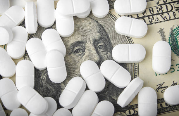 close up of one hundred dollar bill with pills stock photo