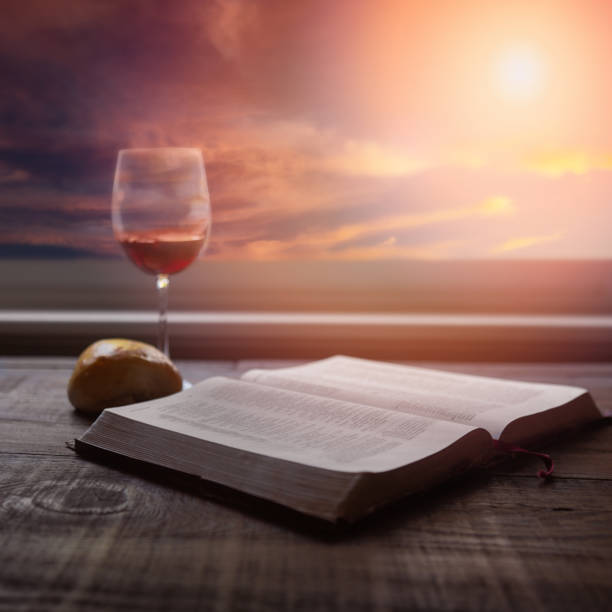 Close up of open Bible, bread and wine for communion with dramatic light. Wood table with sun rays coming through window. Christian image, square format. stock photo